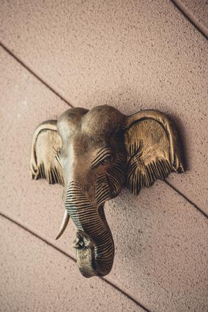 壁の背景 - 真鍮素材の装飾、タイの像に象の頭。色ビンテージ スタイル
