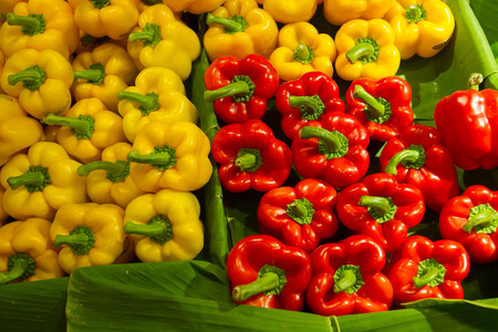 Assorted bell peppers in various colors on the banana leaf at fresh market, autumn vegetables