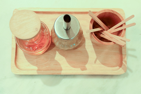 stick at wooden cup with syrup and sugar in clear bottle at wooden tray on a wood table in a coffee shop or cafe