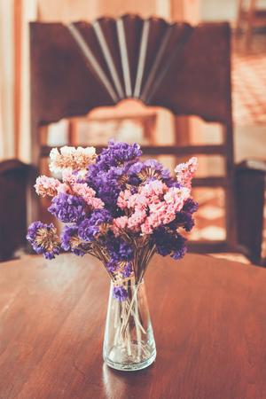 色ビンテージ スタイルのコーヒー ショップでガラスの花瓶にピンクと紫の花の束が、タイの背景をぼかし