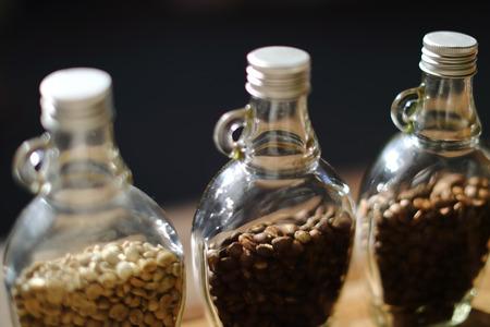 緑色の豆とコーヒー豆のクリアのボトル内部、フォーカスのみ対象ぼかしの背景、チェンマイ、タイ