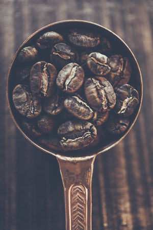 Top view of coffee beans inside Copper spoon at blur wooden background, Colour Retro style 写真素材