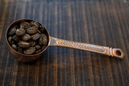 side view of coffee beans inside Copper spoon at blur wooden background, Colour Retro style with copy space