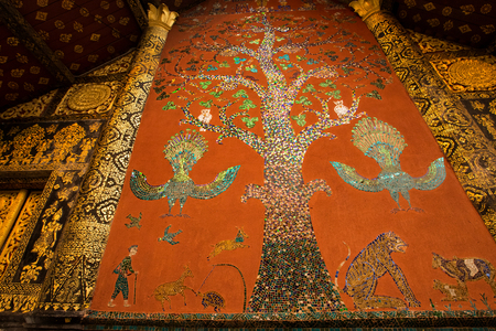 Beautiful the west facade with its painted-mosaic art tree of life  at Wat Xieng Thong temple, Luang Prabang, Laos. 写真素材
