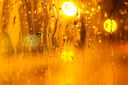 Drops Of Rain On Glass Background at Yellow Light. Street  Bokeh Lights Out Of Focus. Abstract Backdrop 写真素材 - 97018085