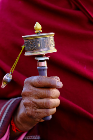 A traditional Buddhist prayer wheel in the hand of an old man in the Bhutan Himalaya. Technic Slow speed shutter show movement of wheel 写真素材
