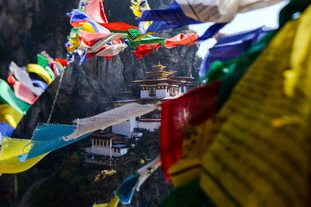 Landscape of Paro Taktsang (Tiger Nest) in Upper Paro Valley, Bhutan. Taktsang Lhakhang is Bhutan most iconic landmark and religious site. foreground prayer flag five color 写真素材 - 97002765