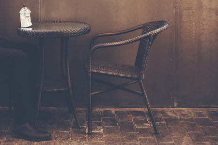 Closeup on coffee table and man sitting at chair coffee cup on table in coffee shop with dark background. copy space 写真素材