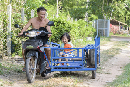 grandaughter: happy granpa and his grandaughter in handmade sidecar bike smiling
