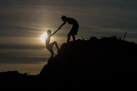 climber: Silhouet van twee jongens geholpen trekken samen klimmen Stockfoto