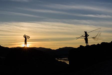 silhouette fishermen holding fishing equipment on his shoulder walked home Stok Fotoğraf