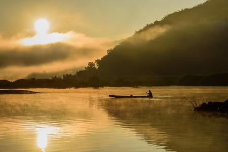 silhouette fisherman on boat in lake