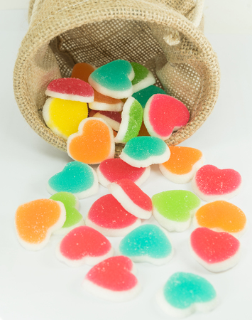 colorful heart sign jelly spread from basket on white background