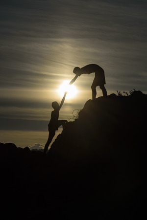 two people with others: Silhouette of two boys helped pull together climbing Stock Photo