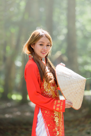 Beautiful vietnamese girl in traditional dress (ao dai) in a park