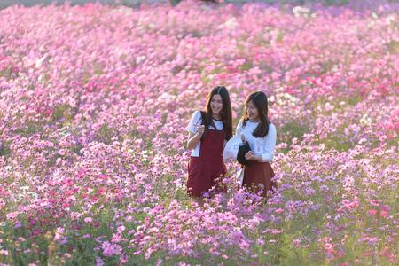 Beautiful girls smiling in cosmos flower field Stok Fotoğraf