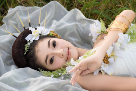 beautiful Asian girl in white gown, adorned her hair with porcupines hair