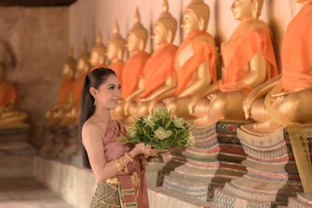 personas saludandose: muchacha tailandesa hermosa en tailandés tradicional homenaje pago traje de una estatua de Buda Foto de archivo