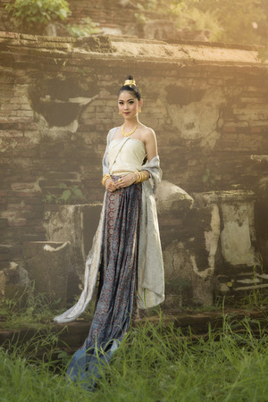 Beautiful Thai girl in Thai traditional costume with old temple background