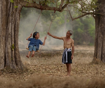 Happy family.Laughing  father and daughter are playing swing under tree