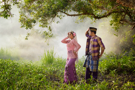Asian Muslim man and woman wearing traditional dress in dancing action