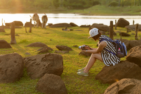 less: beautiful girl backpacker shooting photo by mirror less camera