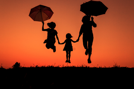 silhouette of a family with umbrella in hand  in the countryside at sunset (Motion Blur) Stok Fotoğraf