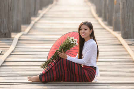 Portrait of smiling beautiful young burmese woman with the traditional dress in u bein bridge mandalay myanmar Stok Fotoğraf - 61394882