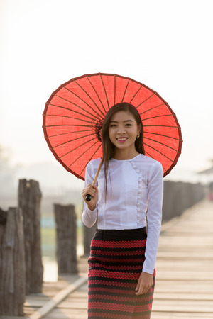 Portrait of smiling beautiful young burmese woman with the traditional dress in u bein bridge mandalay myanmar Stok Fotoğraf - 61393318