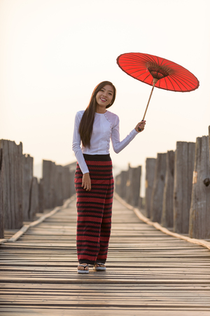 Portrait of smiling beautiful young burmese woman with the traditional dress in u bein bridge mandalay myanmar