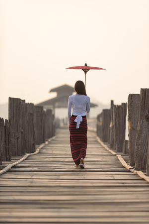 Portrait of smiling beautiful young burmese woman with the traditional dress in u bein bridge mandalay myanmar Stok Fotoğraf - 61393323