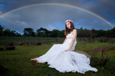 beautiful young woman in white dress with flower on her hair outdoor shot. Portrait of beautiful blond young woman sitting on rock with forest background and rainbow over after rain