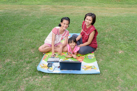 stylus: Smiling family using laptop and tablet with stylus together outdoor