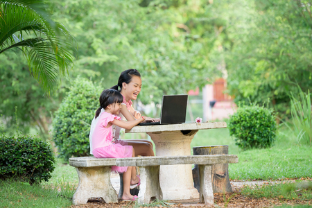 Smiling  two sisters in pink dress using laptop  together Stok Fotoğraf