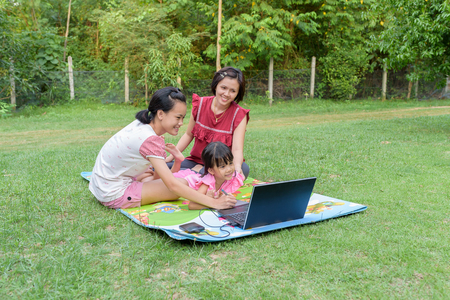 Smiling family using laptop and tablet with stylus together outdoor Stok Fotoğraf - 62152868