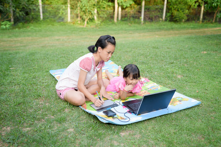 Smiling family using laptop and tablet with stylus together outdoor