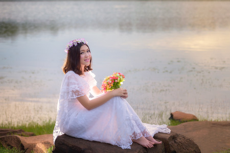 beautiful young woman in white dress with flower on her hair holding flower outdoor shot. Portrait of beautiful blond young woman sitting on rock with water background on sunset Stok Fotoğraf - 62245612