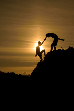 Silhouette of two boys helped pull together climbing Stok Fotoğraf - 62245615