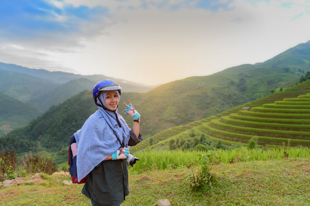 beautiful girl backpacker with terrace rice field background. beautiful smiling girl backpacker with her mirrorless camera standing on terrace rice field high mountain