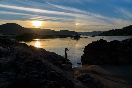 silhouette fisherman holding fishing equipment in action with sundog on blue sky background at sunset