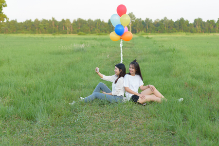 girl with balloons in the green field. Two smiling girls selfie with balloons Stok Fotoğraf - 62496645