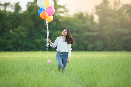 girl with balloons in the green field. Smiling girl play with balloons happily Stok Fotoğraf