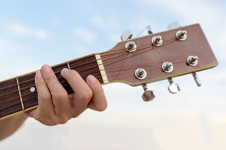 Close-up of womans hands playing guitar on blue sky background Stok Fotoğraf