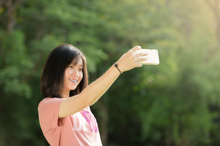 Portrait of a beautiful young girl selfie outdoor with a smart phone