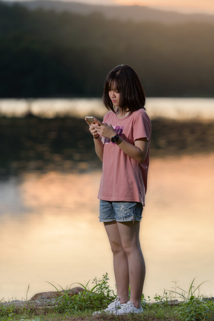 Young woman standting near river at sunset and texting on smartphone Stok Fotoğraf
