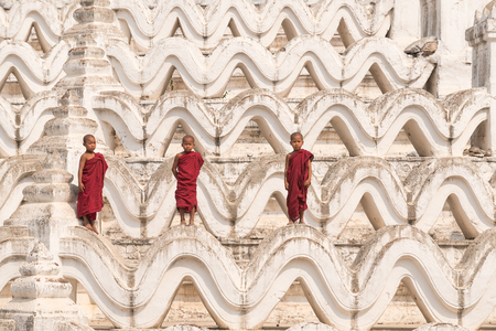 Three Buddhist novices standing on white pagoda in myanmar