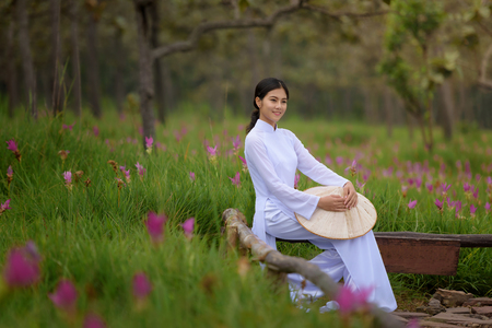 Beautiful vietnamese girl in traditional dress (ao dai) in a park with beautiful pink flower background
