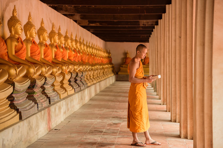 monk standing and reading in temple (public) where have several statues of Buddha Stok Fotoğraf - 64381746