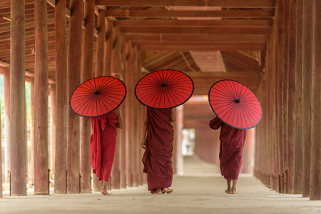Three Buddhist novices with red umbrella on their shoulder are walking inside pagoda in Mandalay Myanmar Stok Fotoğraf