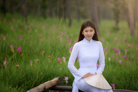 Beautiful vietnamese girl in traditional dress (ao dai) in a park with beautiful pink flower background Stok Fotoğraf - 64381751